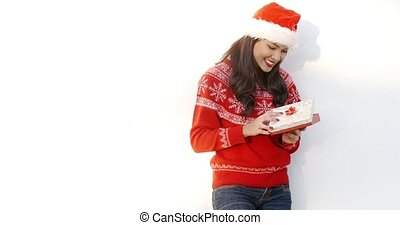 Brunette Girl in Santa Claus Hat Opening Gift She Standing...