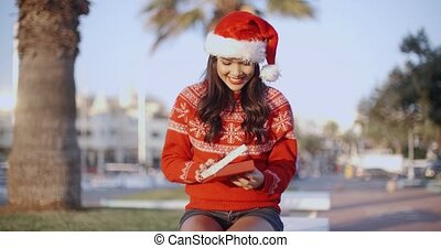 Pretty Young Woman in Santa Claus Hat Sitting on a Bench in...