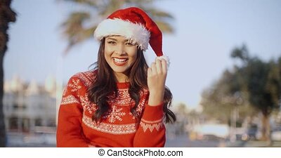 Beautiful Girl in Santa Claus Hat Smiling at Camera She...