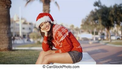 Sexy Girl in Santa Hat Sitting on a Bench in a Park Slow...