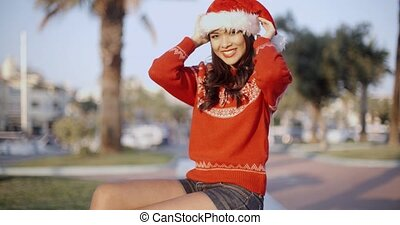 Young Smiling Beautiful Girl in Santa Hat Sitting on a Bench...