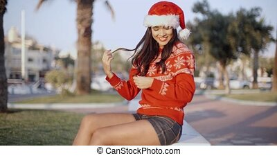 Adorable Young Woman in Santa Claus Hat Sitting in Red...