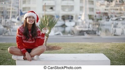 Sexy Girl Sitting on a Bench in Santa Hat - Sexy Brunette...