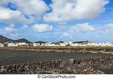 village of Tinajo with volcanoes of Timanfaya national park...