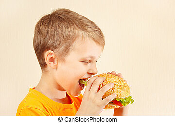 Little funny boy eating tasty sandwich - Little funny boy...