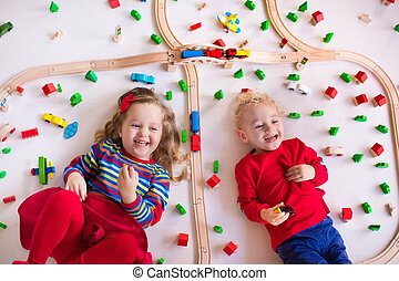 Kids playing with wooden train set - Children playing with...