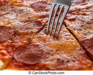 Tasty slice of pizza - Close-up of a piece of pizza and fork