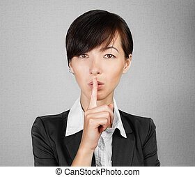 Business secret - Businesswoman making silence sign on gray...