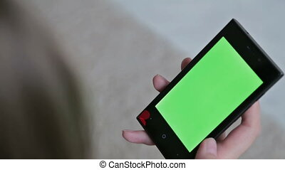 Woman watch on green screen mobile phone closeup. The concept of buying Christmas gifts via the Internet.