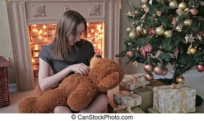 Young woman sitting on the floor and hugs, toss, touch a big...