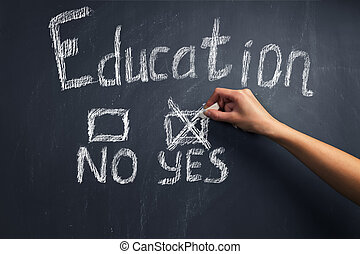 Education: yes or no - Human hand writes education yes on a...