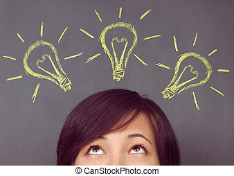 Woman looks up - Young woman looks up on light bulb on the...