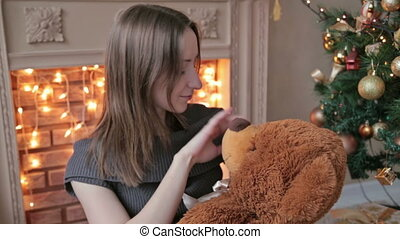 Young woman sitting on the floor and hugs, toss, touch a big teddy bear in Christmas decorations