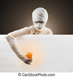 Halloween mummy with a candle and white poster, space for...