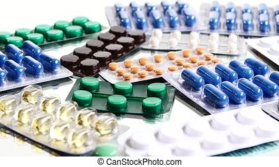 Colorful contraceptive pills, rotation, reflection, close up, on white