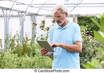 Sales Assistant In Garden Center With Digital Tablet