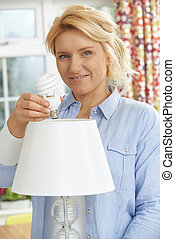 Woman Putting Low Energy Lightbulb Into Lamp At Home