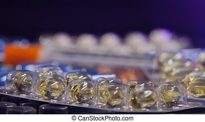 Some different contraceptive pills and two syringes, rotation, reflection, macro, on black, back light