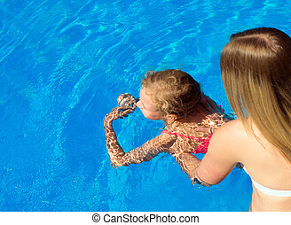 Woman teaching little girl to swim. Place for text.
