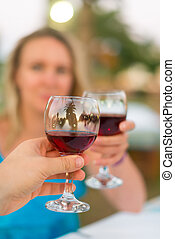 Man and woman clinking their glasses with red wine