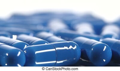 Group of blue medical pills, rotation, close up, on white -...