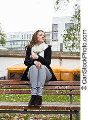 Thoughtful Woman Sitting On Park Bench - Full length of...