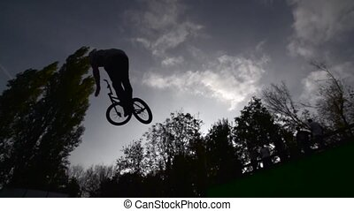 Silhouette of jumper, performing BMX mountain bike sport jump. Slow Motion 400 fps