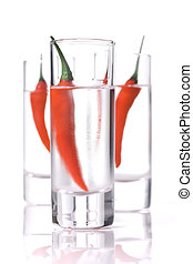 Three Glass of Vodka with red chili pepper over white...