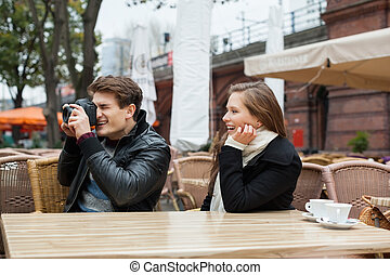 Man Photographing With Woman At Outdoor Restaurant