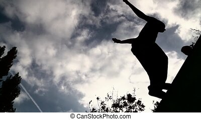 silhouette of parkour jumping man against sky and clouds...