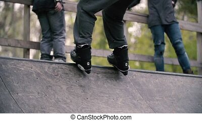 Teen with roller skates performing a stunt on a half pipe...