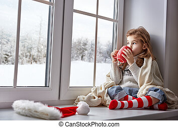 little girl sitting by the window with a cup of hot drink...