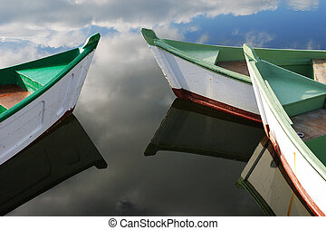 Small white and green wooden boats - Sky reflection and...