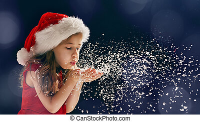 girl blowing on snow - winter time! Happy little girl...
