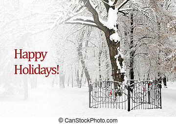 Happy holidays text on background of snow trees in winter...