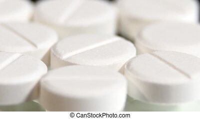 White pills, rotation, macro, on black - White pills and...