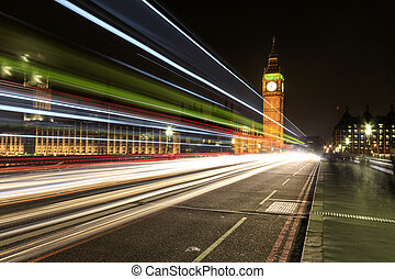 Big Ben at night with the lights of the cars passing