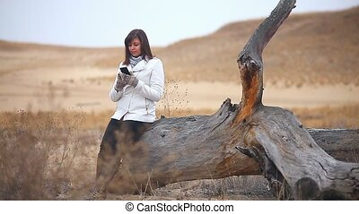 woman searching online smartphone sitting on a dry tree...