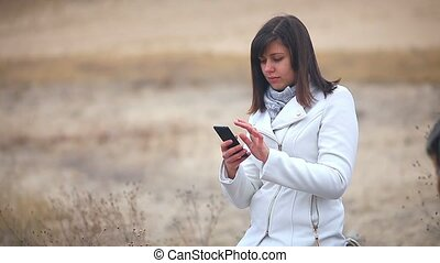 Woman searching the internet smart phone social media nature autumn