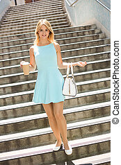 walking with a coffee - young woman walking down steps with...