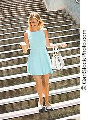 walking with a coffee - young woman walking down steps...
