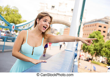 pointing at view - young woman on tower bridge pointing at...