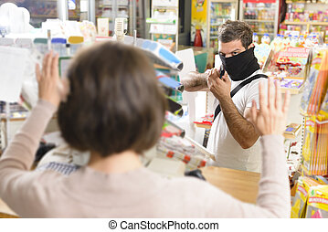 Armed Robbery - Masked thief pointing a gun to sales woman...