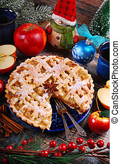 homemade christmas apple pie and decorations on wooden...