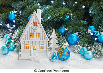 White christmas house with blue decorations in snow