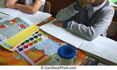 children in the class draw paints in an album drawing lesson...
