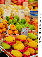 Mangoes - Assortment of fresh mangoes and other fruits on...