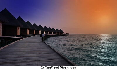 Maldives houses on piles on water at time sunset - Maldives...