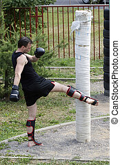 Kickboxer or muay thai fighter equips and trains outdoor. -...