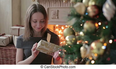Young woman with gifts in front of Christmas tree, HD